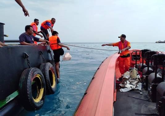 Hulpverleners bezig om wrakstukken en persoonlijke bezittingen uit zee te halen
