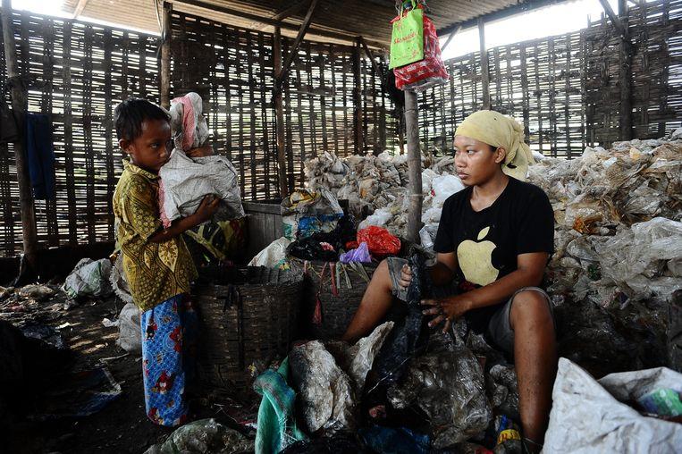 Een vrouw zit bij haar kind terwijl ze zoekt naar spullen om te verkopen tussen het afval in Surabaya, Indonesië. Beeld Getty Images