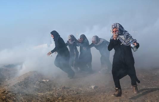 Vrouwelijke Palestijnse betogers zoeken een veilig heenkomen na een aanval met traangas