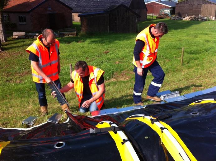 Medewerkers van het bedrijf EcoLoss Barrier maken de nooddijk met grondankers vast aan de dijk bij Gorssel.