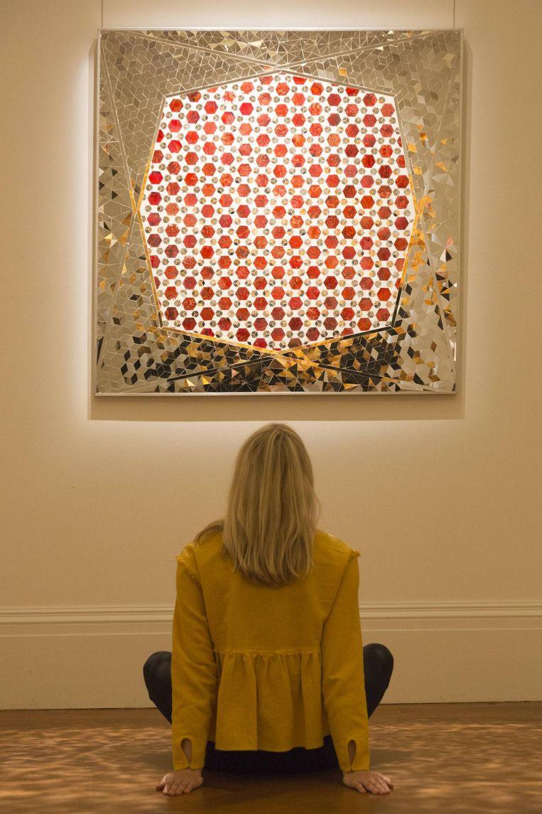 Een bezoeker van Sotheby's in Londen bekijkt Variations on Hexagon of Octagon Mirrors van Monir Farmanfarmaian. Beeld Hollandse Hoogte