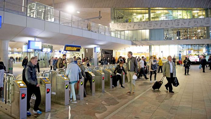 Reizigers passeren de toelatingspoortjes op Rotterdam Centraal