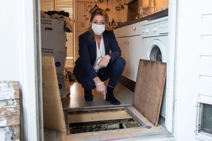 Nadette Beving wijst naar de kruipruimte waar volgens haar de oorzaak ligt van haar gezondheidsproblemen in huis.
