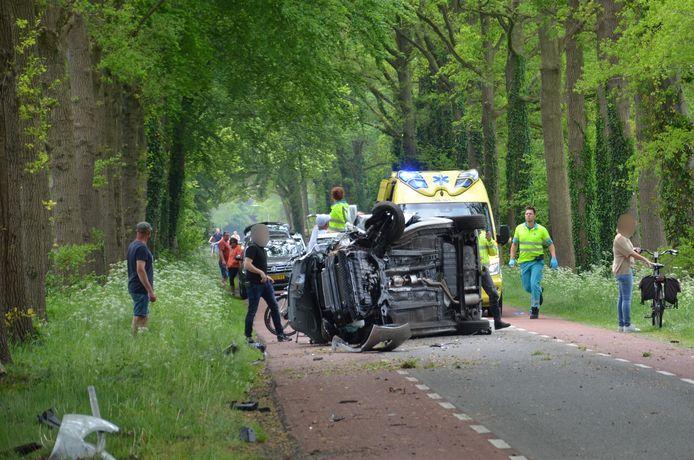 De auto ligt op zijn kant op het wegdek.