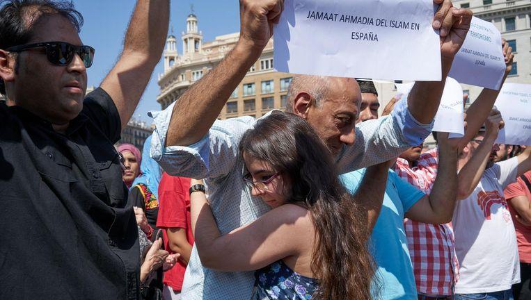 Bewoners van de wijk El Raval zoeken steun bij elkaar na een minuut stilte voor de slachtoffers van de aanslag. Beeld Samuel Aranda