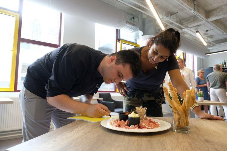 Schepen Jinnih Beels kijkt toe terwijl een van de studenten het kookboek signeert.