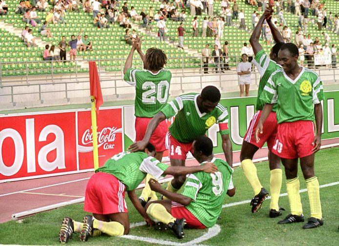 Roger Milla (9) wordt gefeliciteerd door zijn aanvoerder Stephen Tataw (14) na zijn goal tegen Roemenie op het WK 1990 in Bari, Italië.