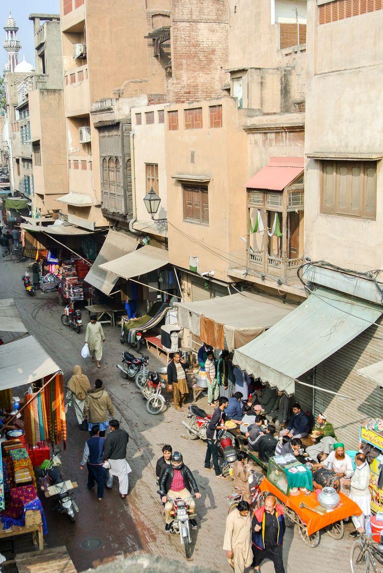 Een drukke winkelstraat binnen de stadsmuren van het oude Lahore. Beeld Haroon Ali