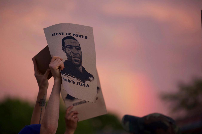Een demonstrant houdt een foto van George Floyd in de lucht.