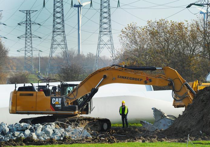 Met diverse specialistische kranen wordt de fundering van de oude windmolens verwijderd.