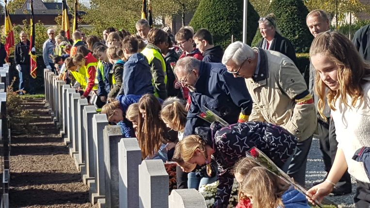 De leerlingen legden aan elk graf een rode roos.