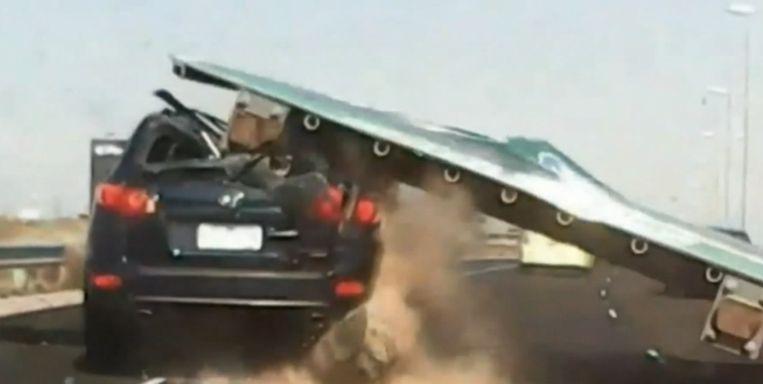 Reclamebord komt plots op rijdende auto terecht in volle spits.