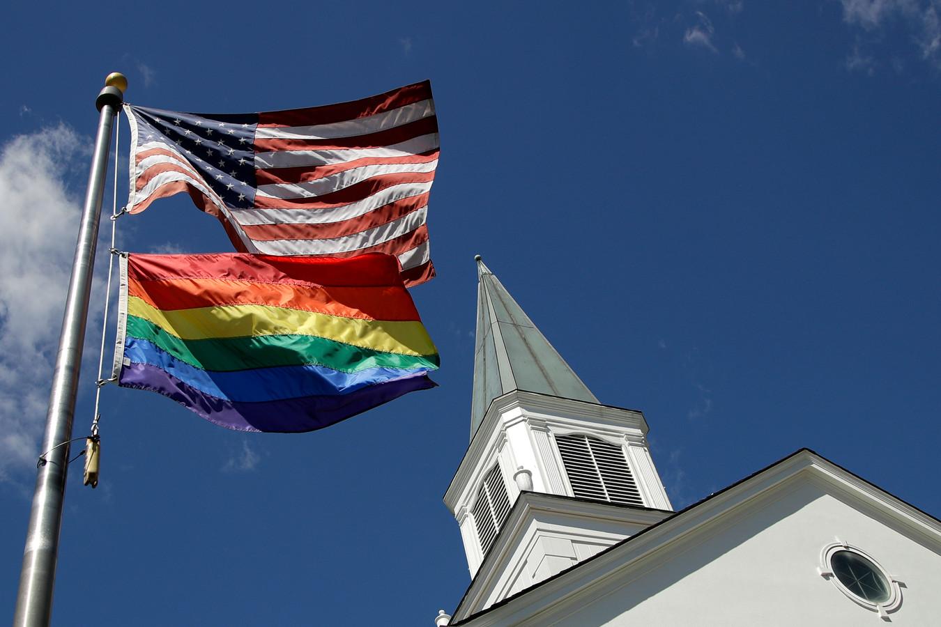 Een Amerikaanse vlag en een regenboogvlag voor een kerkje in de VS. De Trump-regering wilde zorgaanbieders toestaan om zorgverlening aan lhbt'ers te weigeren om religieuze redenen, maar daar heeft de rechter een stokje voor gestoken.