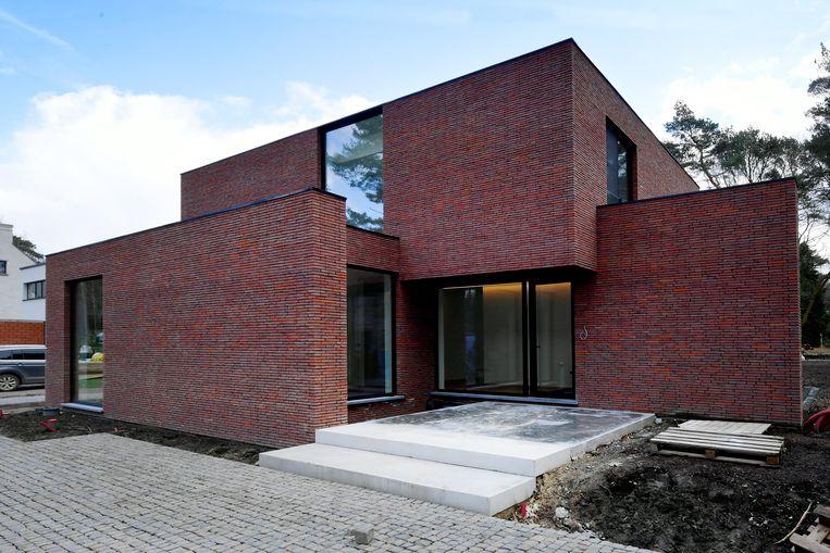 De lichtrode verlijmde baksteen en de slanke, zwarte raamprofielen zetten  het moderne karakter van de woning in de verf.