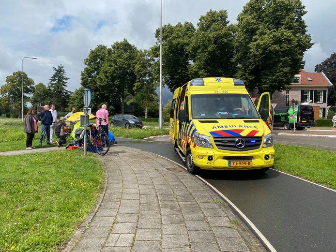 De vrouw wordt op de stoep behandeld door het ambulancepersoneel.