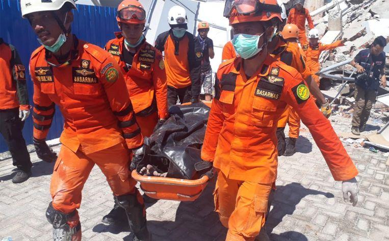 Hulpverleners bergen een van de slachtoffers die gevonden werd bij het hotel.