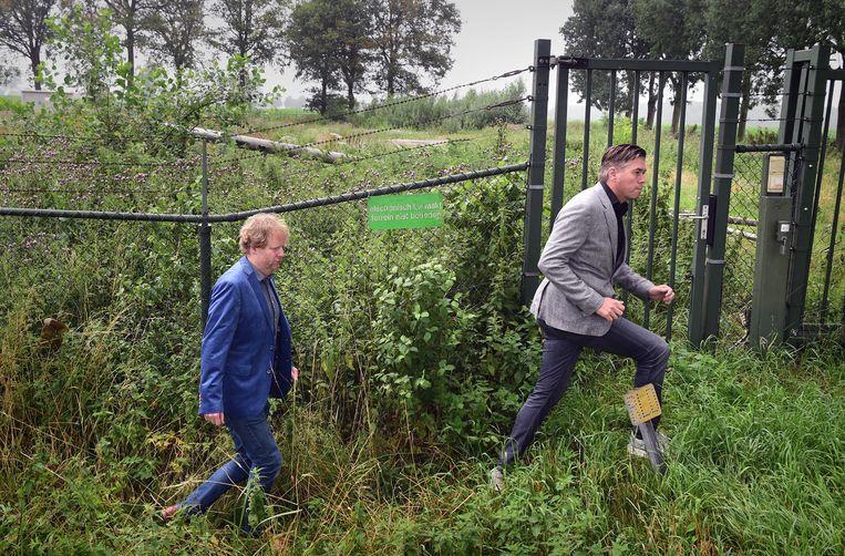 Actievoerders Ruben van der Horst en Edwin Rijkse lopen langs de afrastering van het terrein waar Defensie de radar wil plaatsen.   Beeld Marcel van den Bergh / de Volkskrant