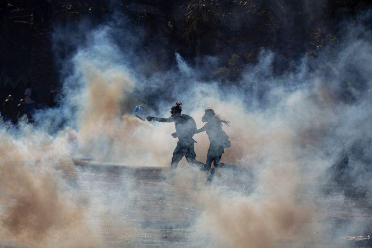 Demonstranten worden door de politie belaagd met traangas.