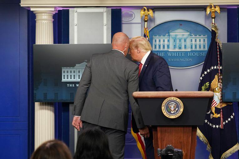 Trump wordt door een medewerker van de Secret Service onderbroken en weggeleid.