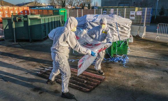 Ieper Asbest moet in speciale zakken. En je krijgt er ook veiligheidspakken bij, zoals hier in Ieper.