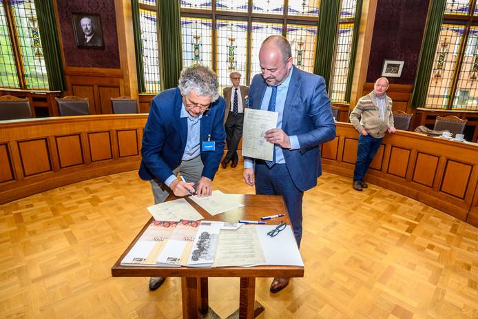Wim Reijnders van het West-Brabants Archief en Paul Mesters CEO Suiker Unie tekenen de archiefoverdracht van de Steenbergse suikerfabriek. Rechts kijkt 'suiker-archivaris' Jan van Meer mee.