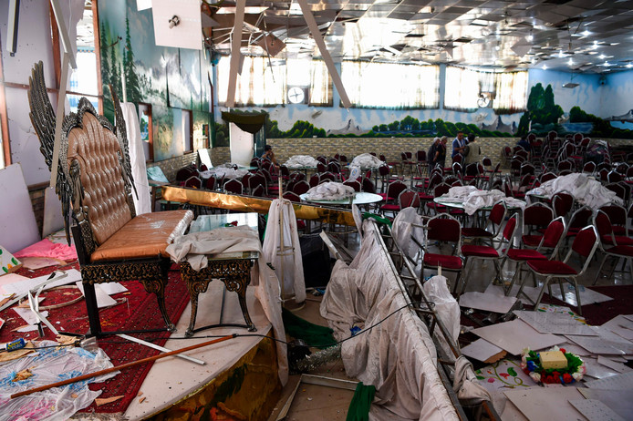 Foto's tonen de ravage in de feestzaal in Kaboel. Temidden daarvan staat de bank waarop het kersverse bruidspaar plaats zou nemen.