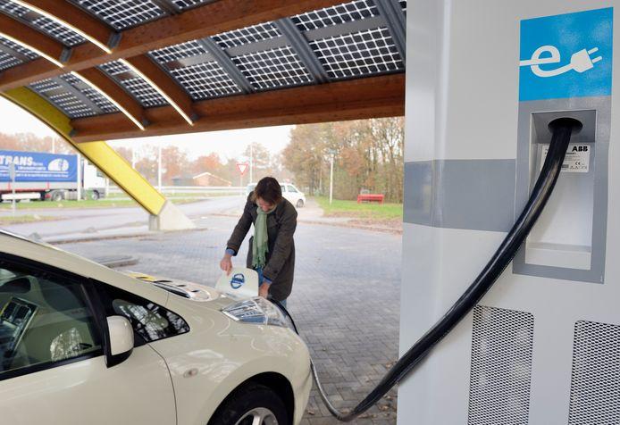 Een automobilist laad zijn elektrische auto.