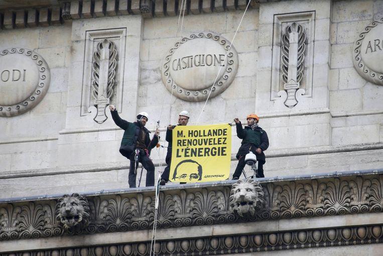 Actievoerders vragen met een spandoek op de Arc de Triomphe aan Hollande 'energie te vernieuwen' Beeld reuters