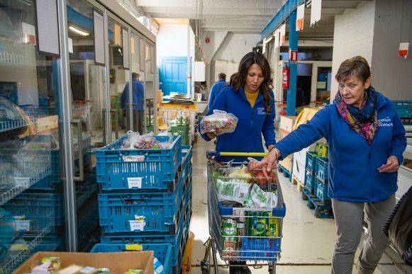 Sandra Bekkari helpt op de voedselbedeling de kar vullen met vrijwilligster Rita.