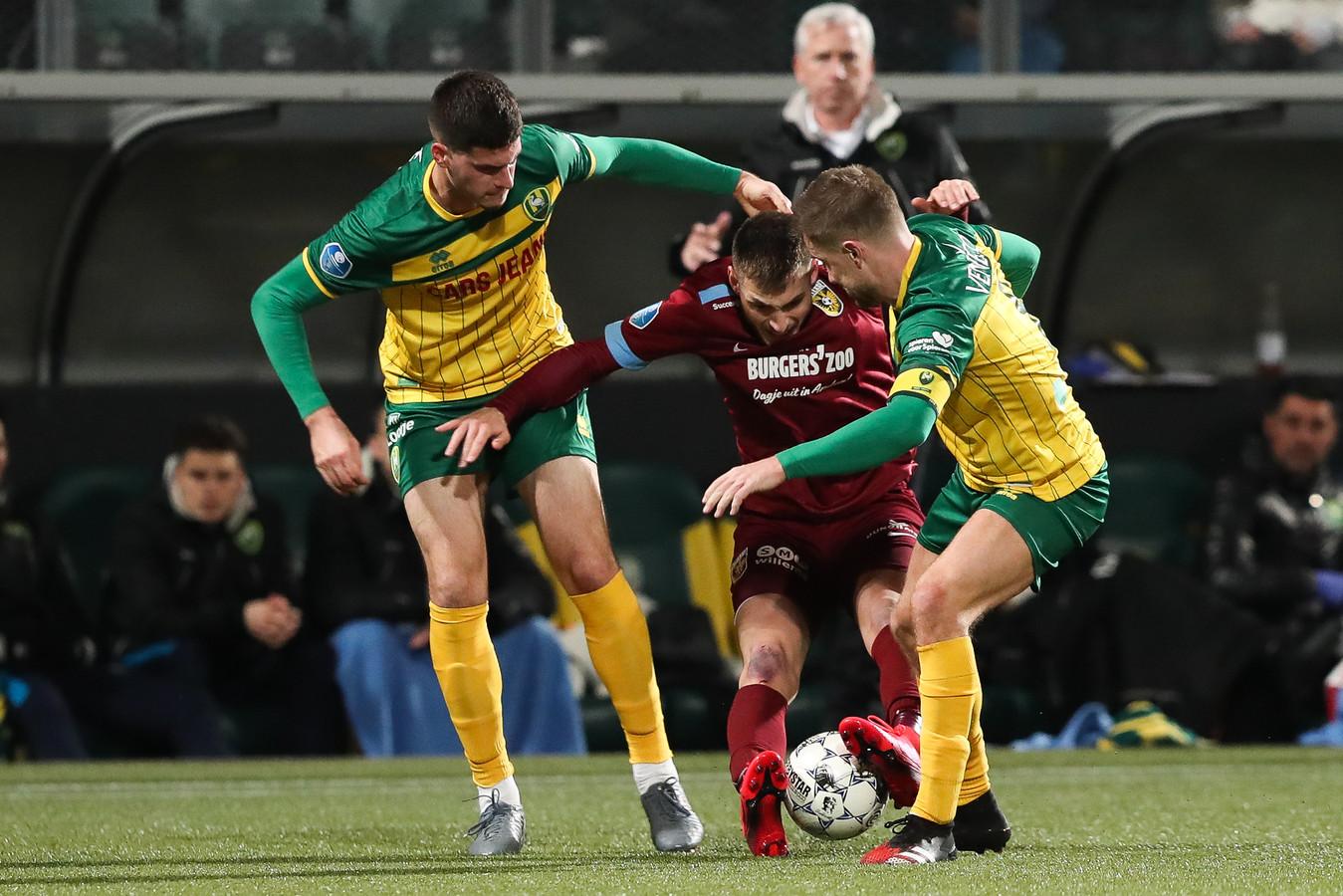 Matus Bero duelleert voor Vitesse met Tudor Baluta (links) en Aaron Meijers van ADO Den Haag.