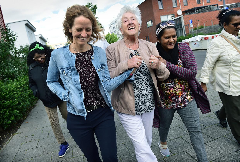 Medewerkers van gezondheidscentrum Lange Hille Rotterdam Zuid (links huisarts Marieke Out) wandelen een uur per week met cliënten. Beeld Marcel van den Bergh