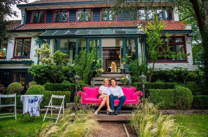 Clarissa Slingerland en Wilfred Barenbrug voor hun woning aan de Delftweg in Rotterdam-Overschie. De roze bank komt oorspronkelijk uit het kantoor van Clarissa's bedrijf, Miss Publicity. Bovenaan de trap staat hond Beer.