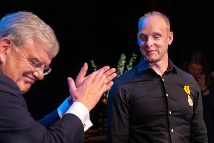 Burgemeester Jan van Zanen applaudisseert voor politieagent Zefanja Engberts, die de Erepenning Menschlievend Hulpbetoon in brons heeft gekregen.