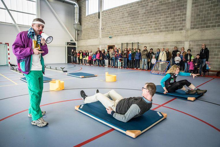 Jan Matthys, ook bekend als Homo Turisticus, in de rol van prettig gestoorde turnleerkracht onderwerpt de ouders aan een parcours in de nieuwe sportzaal.