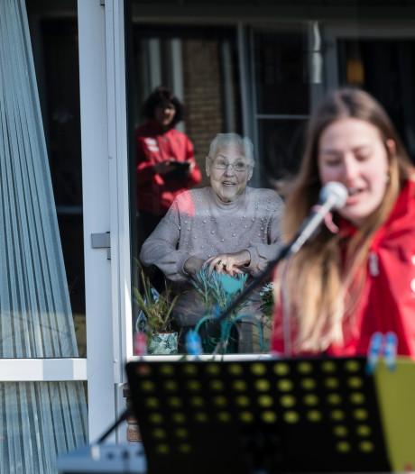 Bewoners Theresiahof Bornerbroek zingen vanachter het glas luidkeels met het bandje mee