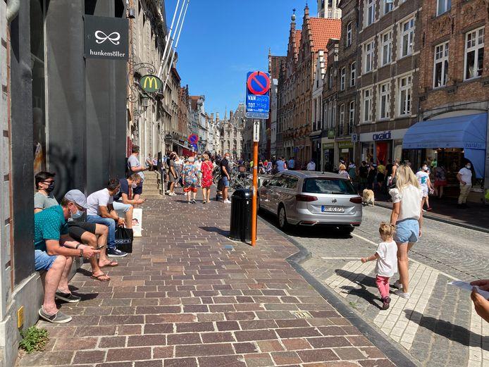 Terwijl hun partners in de Brugse Steenstraat shoppen, tokkelen de mannen buiten op hun smartphones.