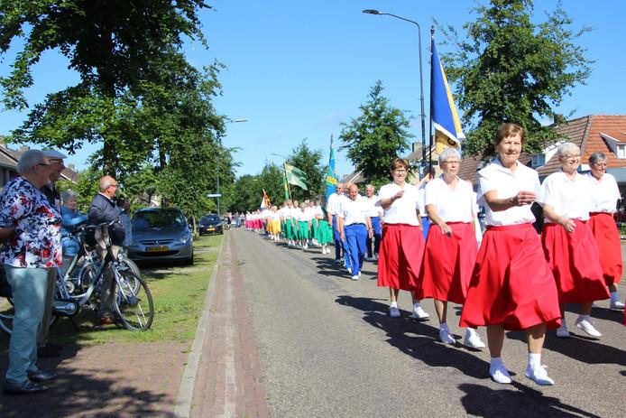 Groepen vanuit Limburg, Noord-Brabant en Gelderland lopen defilé door Odiliapeel. Links kijken Toos en Harrie Hendriks toe hoe er netjes in de maat wordt gemarcheerd.