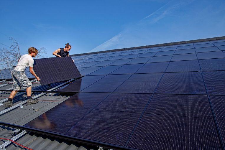 Op het dak van een boerderijstal worden zonnepanelen gelegd.  Beeld Hollandse Hoogte / Dolph Cantrijn