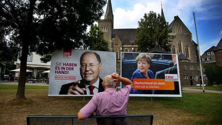 Verkiezingsposters van Steinbrück (links) en Merkel in Olpe. Beeld epa