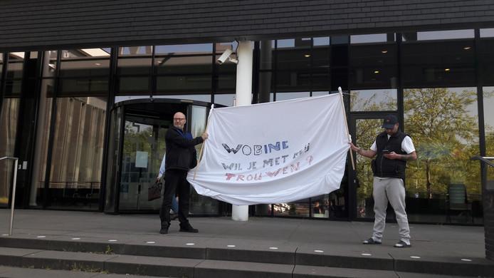 Arie den Dekker (links) geeft een ludieke draai aan zijn demonstratie voor het Osse gemeentehuis.