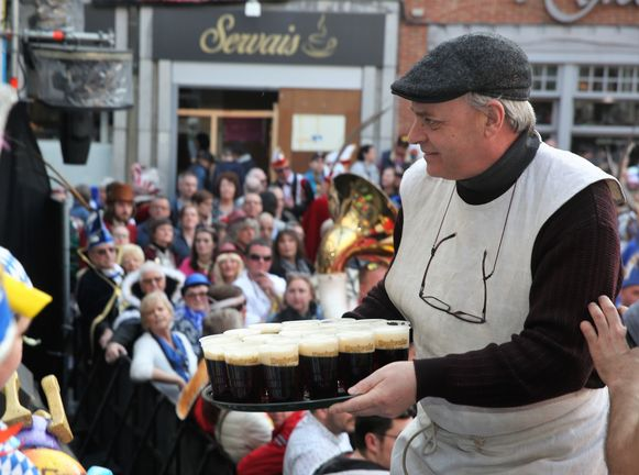 Frank Boon serveert Hals Duivelsbier op de tribune op de Grote Markt bij de start van Carnaval Halle.