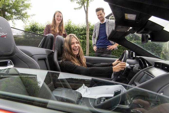 Tess Klaasen mag even in de sportauto zitten. Achter haar de mentoren van het Avila College, Kasper Put en Charlotte Leuveld.