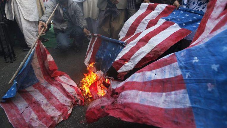 Afghanen verbranden de Amerikaanse vlag uit protest tegen de actie van Amerikanen die de Koran hebben verbrand. Beeld reuters