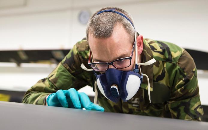 Sergeant August van Gijsel inspecteert het rotorblad van een Apachehelikopter.