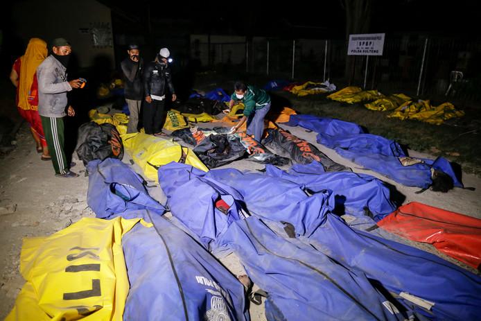 Indonesische mannen bekijken de lichamen van de slachtoffers van de aardbeving en de tsunami, op zoek naar familieleden in Palu, in het midden van Sulawesi. Volgens officiële berichten zijn minstens 384 mensen daarbij omgekomen.