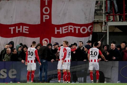 Trainer Klaas Wels en de spelers van TOP Oss proberen hun fans tot bedaren te brengen.