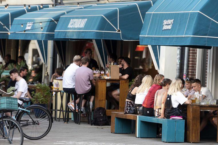 Een terras aan het Hugo de Grootplein. Vanaf maandag alleen toegankelijk na registratie. Beeld ANP