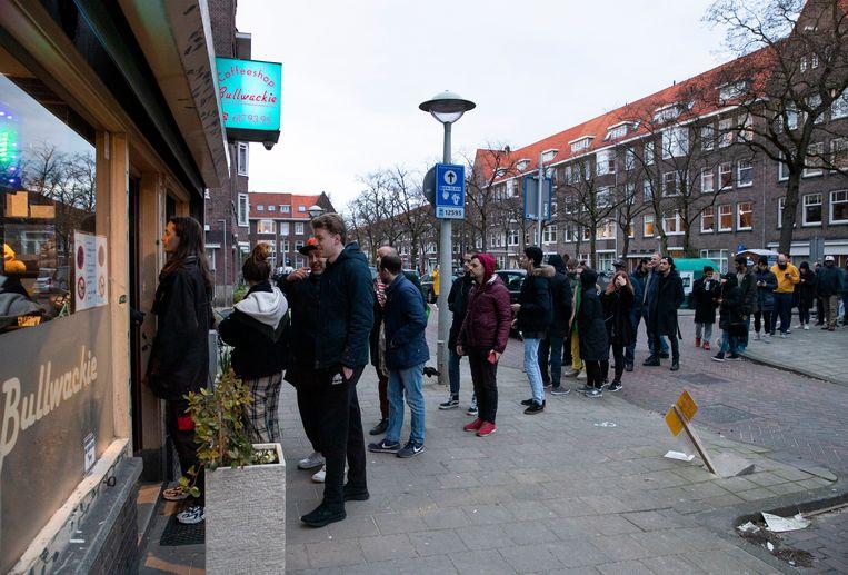 Een rij voor coffeeshop Bulwackie in Amsterdam. Klanten halen gauw nog wiet voor de deuren drie wekend dichtgaan. Beeld AP
