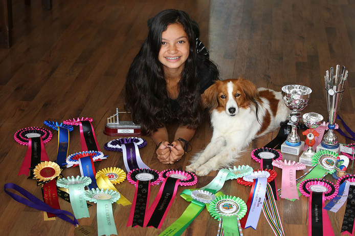Quinty Kdise en haar hond Holly tussen al haar gewonnen bekers en rozetten.