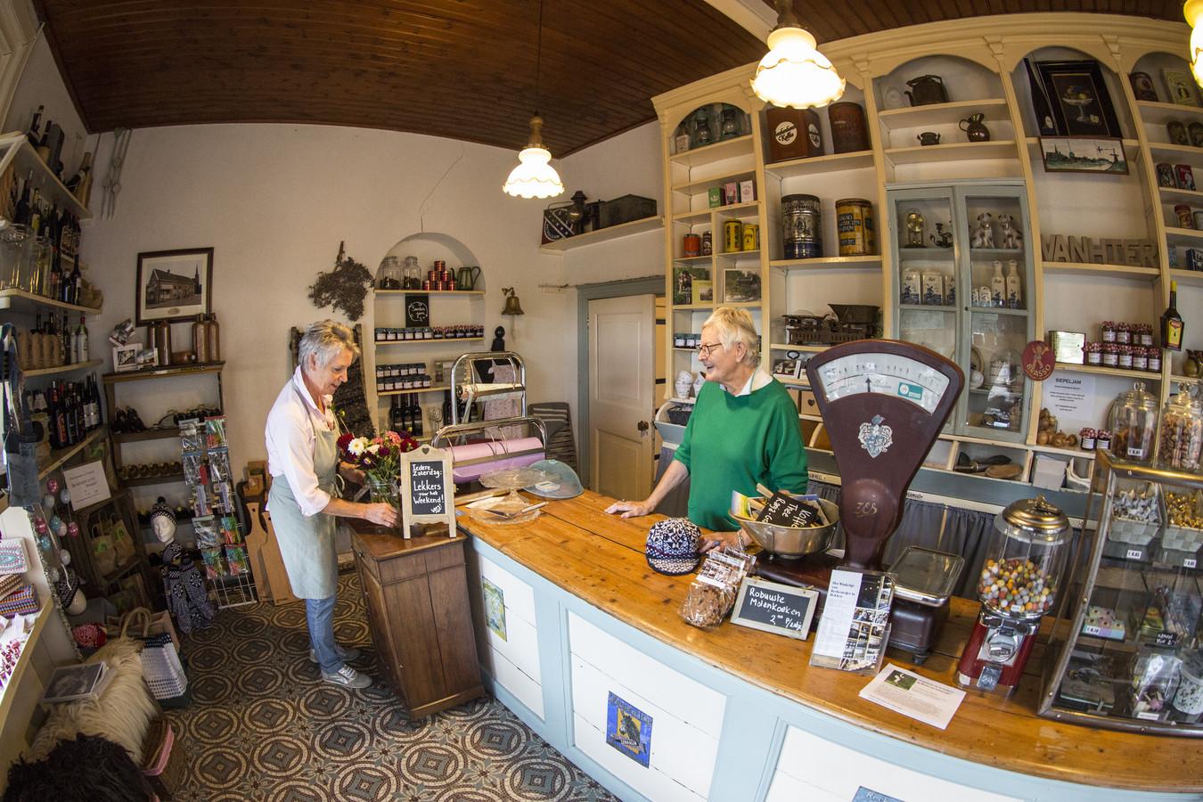 Het vroegere kruidenierswinkeltje van  Kerkemeijer pal naast het gelijknamig café is deze week een  jaar in gebruik bij vrijwilligers die er van alles verkopen. Anja van Rijnsoever (l) en Ria Kerkemeijer lopen het aanbod voorafgaand aan het volksfeest even na.